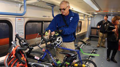 Greg Hinchliffe of Baltimore secures his bike and helmet onto a bike rack inside the MARC train's bike car in December 2015.