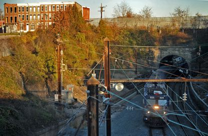 From the overpass on Monroe Street, looking east as a train emerges from the Baltimore & Potomac Tunnel that runs under Winchester Street.
