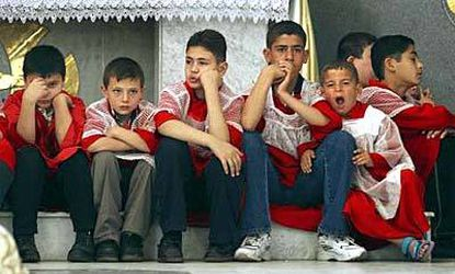 Altar boys at Sacred Heart Chaldean Catholic Church in Baghdad struggle to pay attention during Easter services. Among the remaining Christians in Iraq, feelings are mixed about the war.