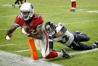 Arizona Cardinals wide receiver John Brown (12) scores a touchdown as Baltimore Ravens cornerback Jimmy Smith (22) defends during the second half of an NFL football game, Monday, Oct. 26, 2015, in Glendale, Ariz.