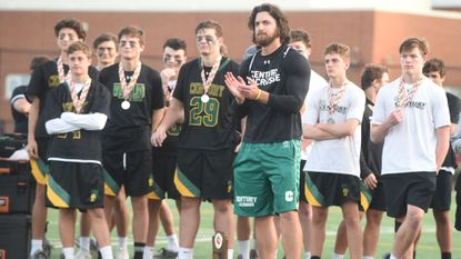 Century head coach Jeremy Benson, with the finalist trophy at his feet, stands with his players as they appluad the opposition, following the Knights loss to Glenelg during the Class 2A boys lacrosse state championship game at Paint Branch High School on Tuesday, May 21.