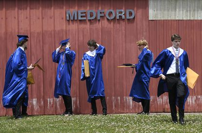 Liberty graduates gather outside following their graduation ceremony at the Carroll County Agriculture Center in Westminster Tuesday, June 1, 2021.