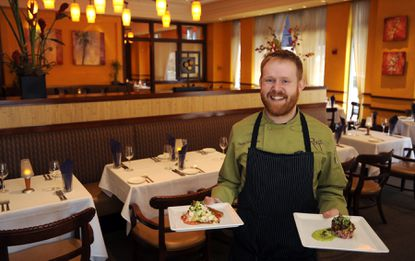 "Patrick ""Opie"" Crooks, who has been hired as Shoo-Fly's chef de cuisine. Crooks is pictured in one of the dining rooms at Roy's."