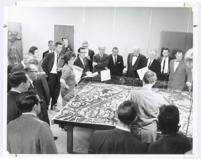 Jim Rouse, center with glasses and arms folded, presents the plans for Columbia, as well as a model of Town Center and the first village, to the Howard County commissioners and other county officials Nov. 11, 1964.
