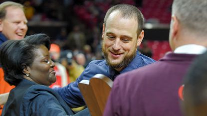 Poly boys basketball coach Sam Brand receives the state championship trophy after the Engineers beat Milford Mill in the Class 3A state championship game at Xfinity Center in College Park in March.