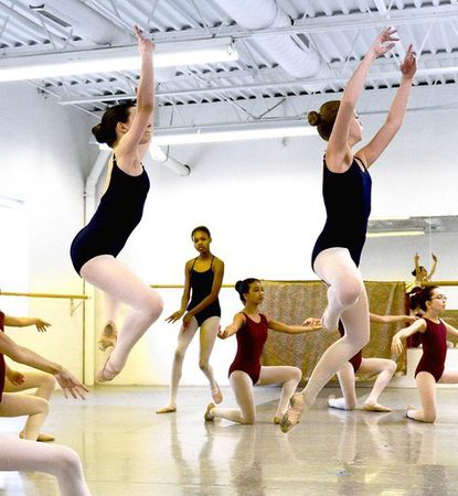 """Jennifer Strakna, 14, of Columbia, left, and Adele Yodzis, 13, of Ellicott City, leap into the air during practice for """"The Nutcracker"""" at Central Maryland Youth Ballet."""