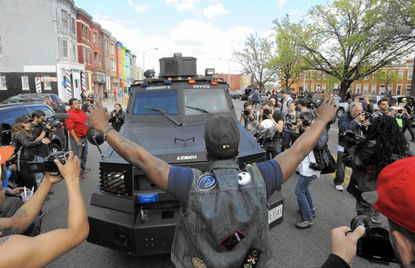Protesters face a police vehicle Tuesday, April 28, 2015, in Baltimore. Maryland's governor vowed there would be no repeat of the looting, arson and vandalism that erupted Monday in some of the city's poorest neighborhoods. (Lloyd Fox/The Baltimore Sun via AP)