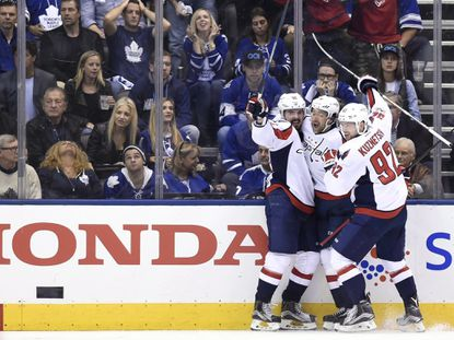 Capitals center Marcus Johansson (90) celebrates with right wing Justin Williams (14) and center Evgeny Kuznetsov (92) after scoring the overtime game-winner against the Maple Leafs during Game 6.