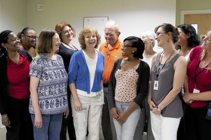 Executive Director Andrea Ingram, center, is surrounded by employees at the Grassroots Crisis Intervention Center on Freetown Road in Columbia.