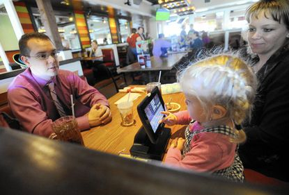 Abby Dillman, 3, occupies herself with the Ziosk device while eating lunch with her parents, Chris and Becky Dillman, of Mount Airy, Sunday at Chili's in Eldersburg.