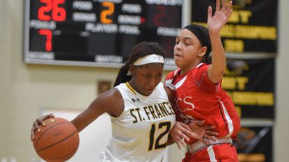 St. Frances #12 Delicia Pinnick drives around Roland Park #22 Aniyah Carpenter in the first half of the No. 3 Roland Park Country School at No. 1 St. Frances Academy girls basketball game. St. Frances' game with No. 2 McDonogh has been postponed because of the icy weather.