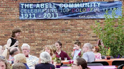 Meg Stoltzfus, standing, has lived on Abell Avenue for 10 years and was more than happy to attend the community's 100th birthday part on the bell Open Space on June 18.