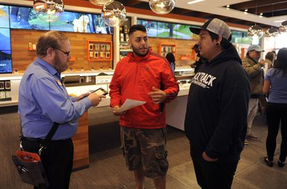 Mark Whiteford, left, a retail sales consultant, works with Juan Martinez, center, and Kevin Cerda, right, both of Baltimore, as they purchase the new Apple iPhone 6 at the AT&T Store in Timonium.