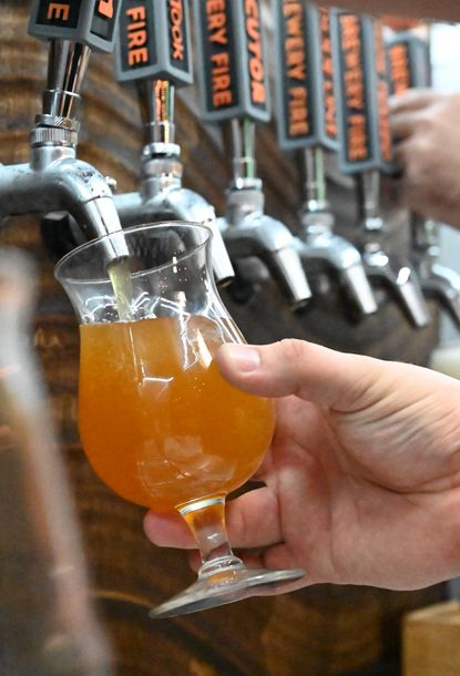 A beer is poured from its tap.