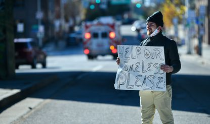 Dustin Rogers holds a sign during a protest last year over plans then to close an encampment beneath the Jones Falls Expressway.