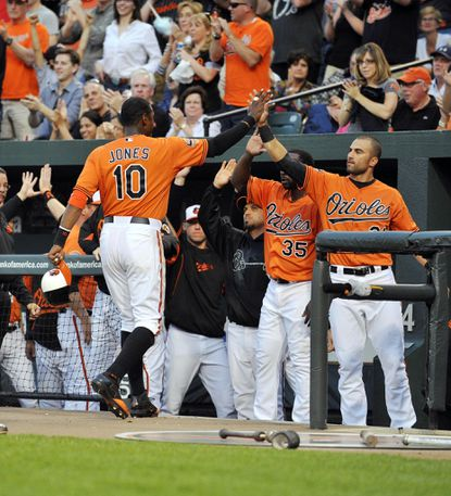 Adam Jones is congratulated by teammates, including Nick Markakis, right, and Bill Hall, second from right, after scoring during the Orioles' two-run second inning, which featured three errors by the Rays.