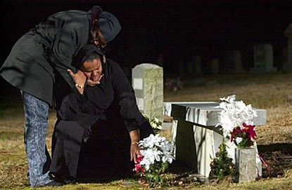 Barbara Jackson (right) is comforted by friend Adria Wilson during a visit to Quortez Jackson's grave. After her son's death, Jackson moved so she could be closer to his final resting place.