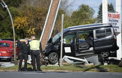 Police work at the scene of a crash that left a van raised up off its wheels at the intersection of westbound Md. 140 and Sullivan Road in Westminster Wednesday, Nov. 18, 2020.