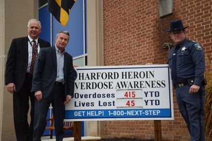 Sheriff Jeffrey Gahler, right, is pictured with Rod L. Kornrumpf, Regional Executive Director-Behavioral Health, UM Upper Chesapeake Health, far left, and Harford County Executive Barry Glassman, in front of the Harford overdose awareness sign at the sheriff's headquarters in Bel Air. The signs, which are positioned at each sheriff's precinct, have been updated with the 24/7 crisis hotline number, 1-800-NEXT-STEP.