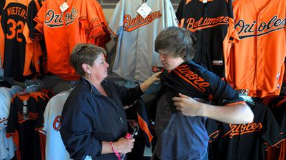 Tammy Kolb helps her 13 year old son Ryan Kolb try on a jersey at the Majestic Team Store, in the warehouse at Camden Yards. With the Orioles possible headed for the play-offs the sales of team merchandise has been skyrocketing.