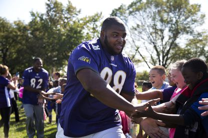 Nose tackle Brandon Williams greets students of Baltimore Highlands Elementary School after finishing an obstacle course as part of a Play 60 event.