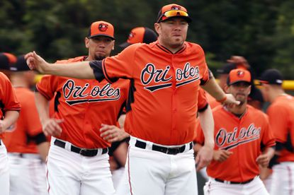 Baltimore Orioles pitcher Chris Tillman warms up with teammates during a baseball spring training workout in Sarasota, Fla., Feb. 25.