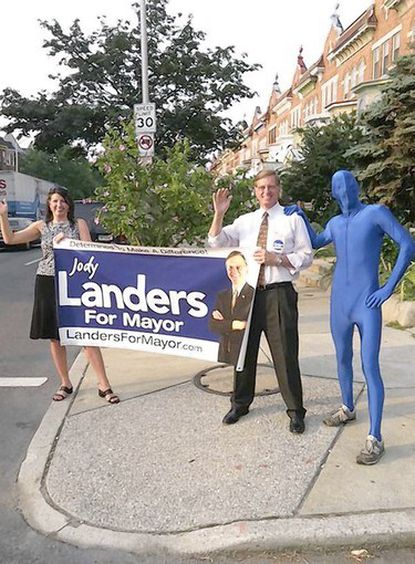 """Blueman, a mysterious figure in a full body Spandex suit, is helping mayoral candidate Joseph T. """"Jody"""" Landers with his weekday morning car waves."""