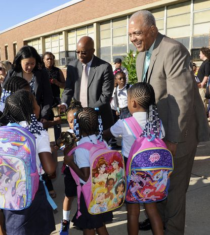 New city schools CEO Gregory Thornton (right) greets children on the first day of school at Holabird Academy.