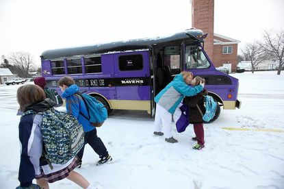 Jody Aldave kisses her daughter, Rebecca, 8, goodbye after Jody and her husband, John, dropped off their children at St. Mark School in their purple Ravens Game Time bus in Catonsville, on Friday.