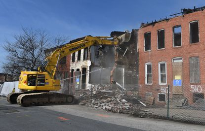 "Demolition crew knocks down row houses after ceremony where former Baltimore Mayor Catherine Pugh operated the excavator to start the demolition of a block of vacant row houses at 502-522 Baker Street in west Baltimore as part of her ""Vacants to Value,"" A New Era of Neighborhood Investment initiative."
