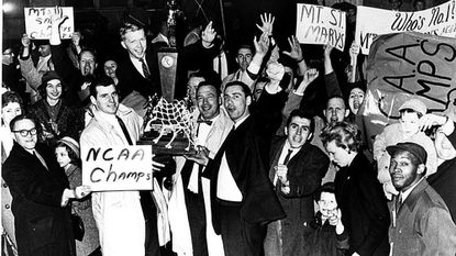 Coach Jim Phelan gets help from players John O'Reilly and Dick Talley in hoisting the trophy after guiding Mount St. Mary's to the 1962 NCAA College Division national championship.