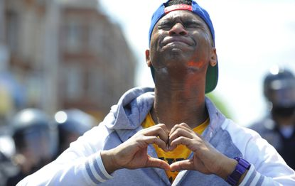 Devante Hill of Baltimore makes a heart with his hands after he was hit with pepper spray after someone threw a bottle at police.