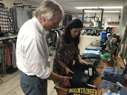 Maryland Comptroller Peter Franchot, left, looks for a pair of jeans with Beth Pocalyko, owner of John's Men's Clothing in Bel Air, during the state's back-to-school tax-free shopping days in August 2019.