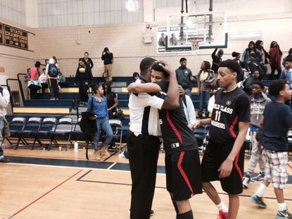 Woodlawn's TJ Owens gets a hug from his dad, Teron, after the Warriors defeated Catonsville, 69-63. Owens scored 18 points against the school where his dad coaches junior varsity and played on its 1992 state championship team.