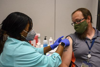 Georgia Tech employee Adam Jackson receives a Pfizer COVID-19 vaccination on campus in Atlanta. U.S. colleges are weighing vaccine mandates for students and staff, an issue that employers across the nation are grappling with. (AP Photo/Danny Karnik)