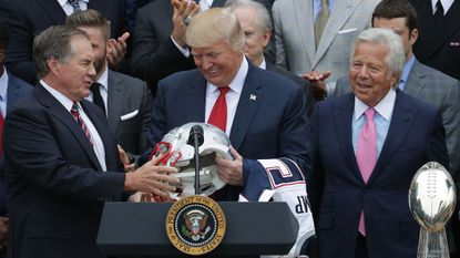 In this April 19, 2017 file photo, New England Patriots coach Bill Belichick, left, and team owner Robert Kraft, right, present a football helmet to President Donald Trump during a celebration of the team's Super Bowl victory on the South Lawn at the White House in Washington. Belichick on Monday declined to receive the Presidential Medal of Freedom from President Donald Trump.