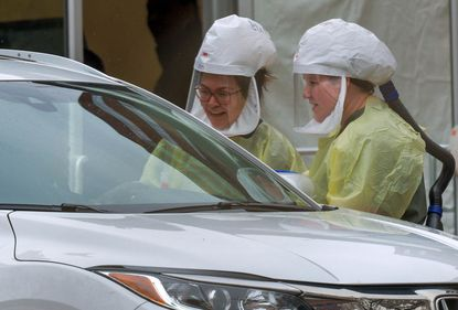 Johns Hopkins Hospital nurses talk with a patient at a drive-though coronavirus testing site.