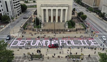 Protestors painted, in large pink lettering, a demand to DEFUND THE POLICE during a demonstration last year on Gay Street, near City Hall in Baltimore.