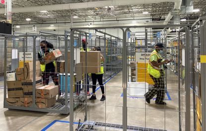 Workers in Amazon's new Baltimore delivery station on Van Deman Street load packages to be handed off to van drivers for the day's routes to customers. (Lorraine Mirabella/Baltimore Sun).