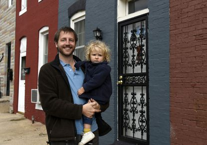 Craig Bettenhausen stands near the rowhouse he bought and renovated to lease out in Remington. He is holding his daughter Elsa, who is almost 2.