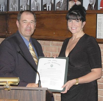 Bel Air Mayor Edward Hopkins presents a proclamation to Lisa Limberger, founder and president of Healthcare's Information Edge, during the July 15 town meeting. The proclamation was an official welcome to the company from the Board of Town Commssioners.