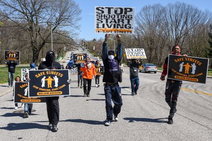 Members of Safe Streets Belair-Edison held a youth-led community march through the street on Saturday, April 3, 2021. The neighborhood hasn't had a shooting or homicide since December 2020, according to site director Dante Johnson.