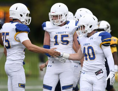 From left, Liberty defensive lineman Tanner Parrott, linebacker Kevin Lynch and linebacker McClain Butler celebrate a sack against St. Paul's in the first half of a high school football game.