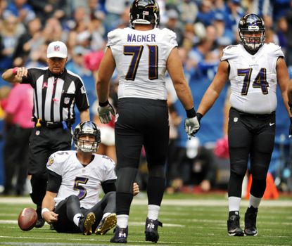 Joe Flacco sits on the ground in front of linemen Rick Wagner and James Hurst after a sack in the first quarter.
