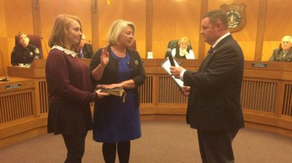 Casi Tomarchio, center, is sworn in to the Havre de Grace City Council Monday by Mayor William Martin as her daughter, Alexandra, holds the Bible.