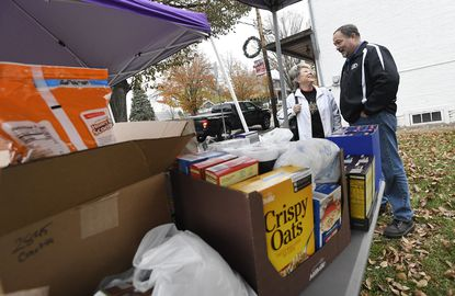 New Windsor mayor Neal Roop, right, chats with Peggy James of Westminster who stopped by to drop off a donation of canned goods during the fourth annual Mayor on the Square Food Drive Friday, Nov. 22, 2019 where Roop conducts town business out of the office while accepting donations of food and coats. The drive benefits the New Windsor Food Bank and The Shepherd's Staff's Call for Coats.