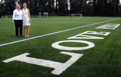 Yeardley Love's mother Sharon Love, left, and sister Lexie, right, stand near the new turf field at Notre Dame Preparatory School that is named for Yeardley, a NDP graduate who died in May 2010. The $1.2 million field was built with funds raised by Notre Dame Prep and the One Love Foundation, and will be dedicated on Sept. 9.