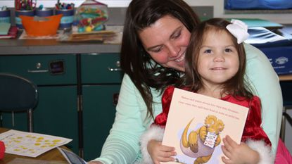 """Brooke Schrock, reads with daughter, 2 year-old, Jessya, during their weekly School Readiness session at Bakerfield Elementary School in Aberdeen. Jessya gets to keep this book, """"How Do Dinosaurs Say I Love You,"""" thanks to the generosity of Harford County Education Foundation."""