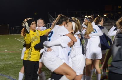 Howard's girls soccer team celebrates on the field following the team's 2-0 victory over South River on Saturday night in the 4A state semifinals.