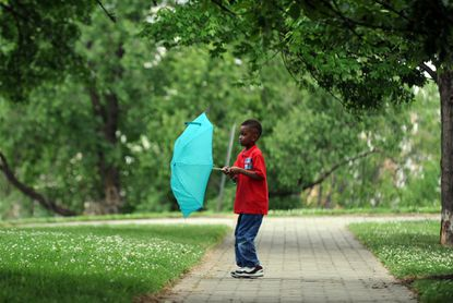 Spencer Smith, 6, gets his umbrella ready for the rain as he and his mom, Farrah Spruill, not pictured, enjoy the Inner Harbor on Federal Hill.